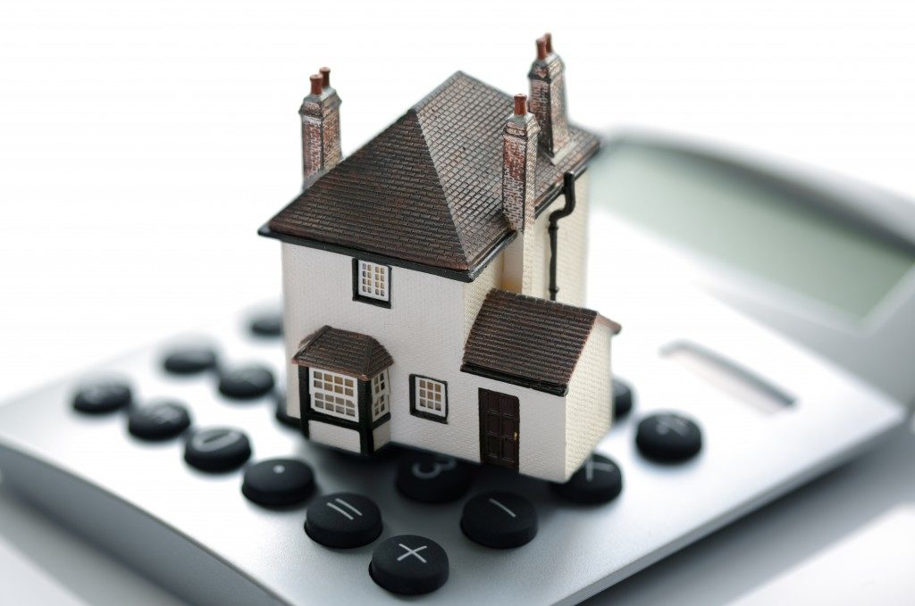 house miniature placed over calculator