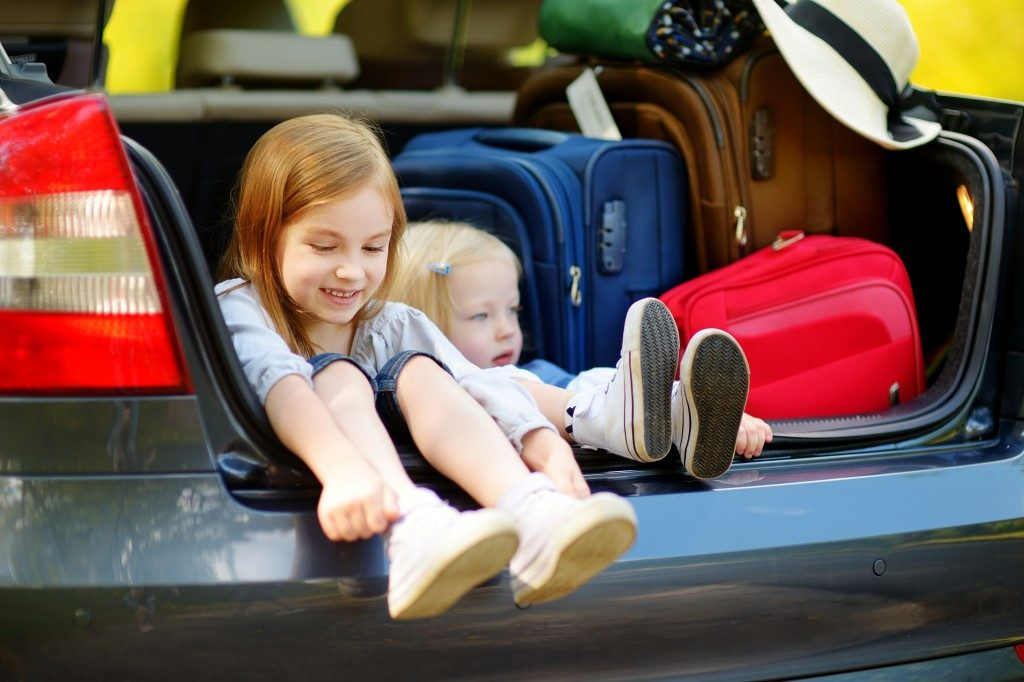 little girls in the trunk with luggages