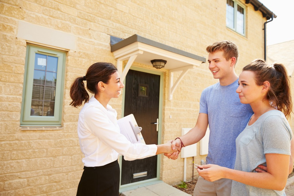 young home buyers handshaking real estate agent