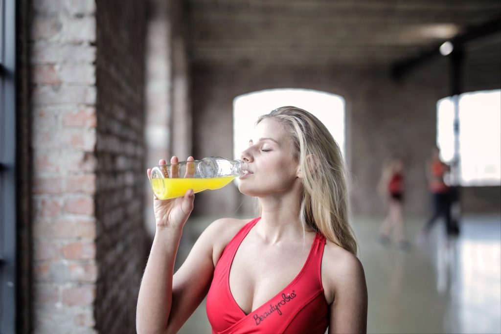 woman drinking juice after work out