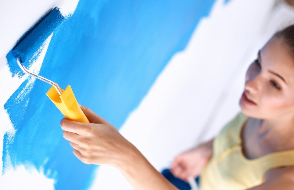 woman painting the white wall blue