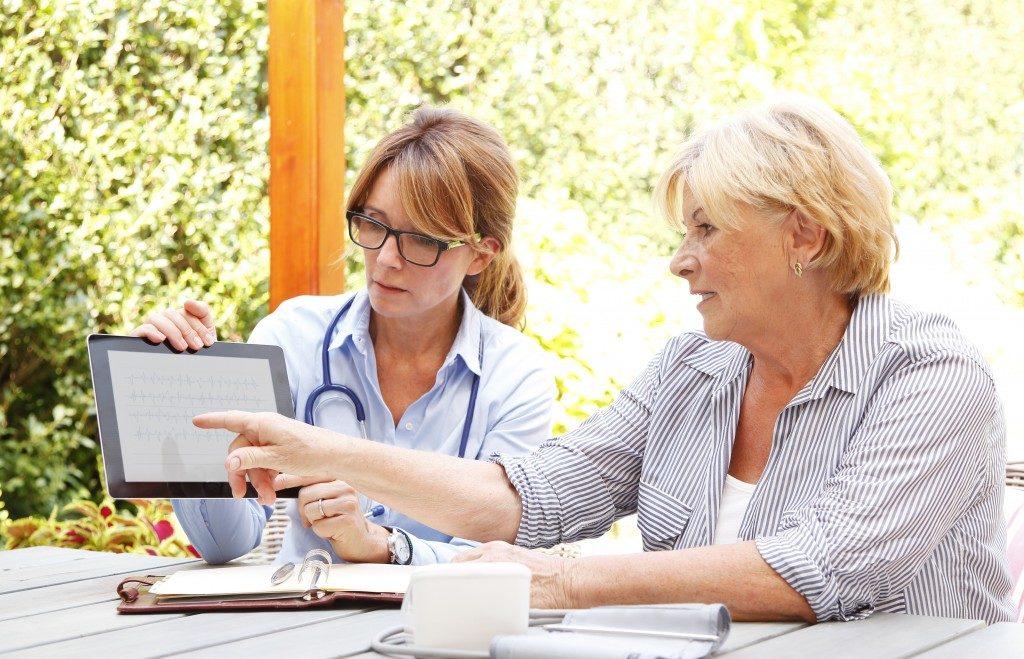 Doctor helping elderly use an Ipad
