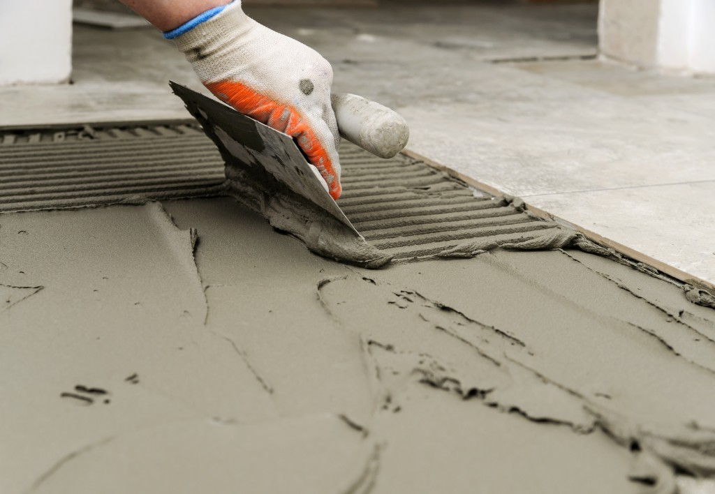 Troweling mortar onto a concrete floor in preparation for laying floor tile