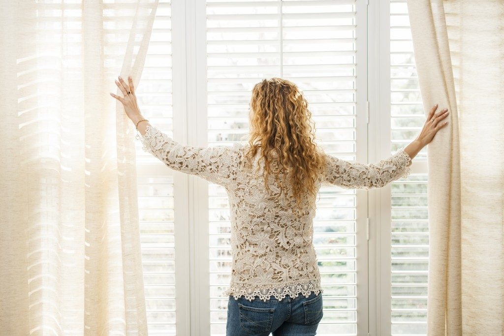 woman parting the curtains of a large window