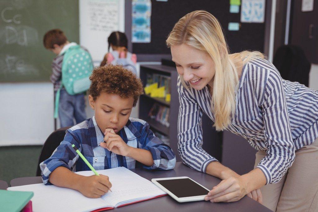 teacher sitting beside her student