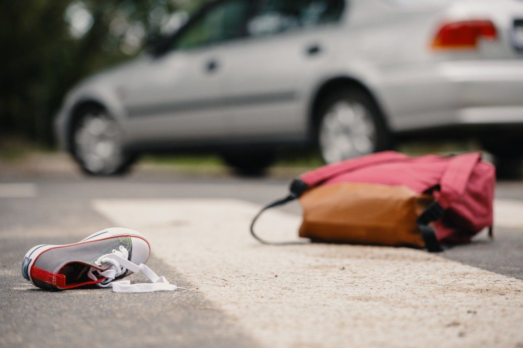 Shoe and bag in the foreground to signify car crash