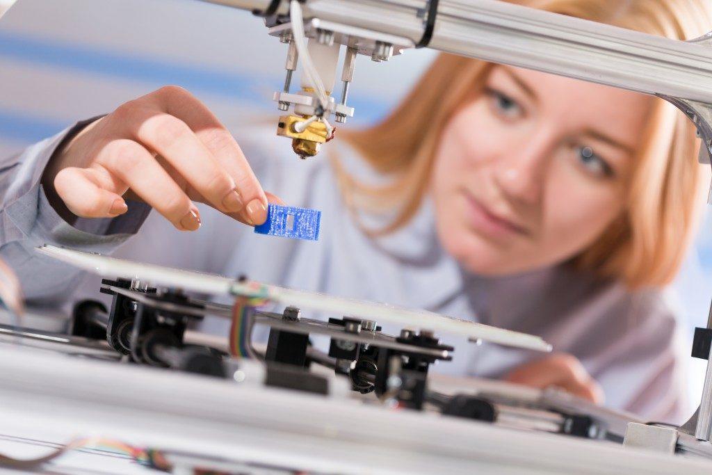Woman using a 3D printer