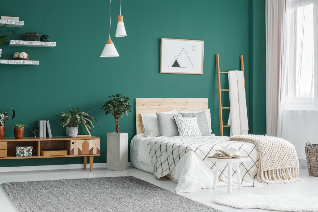 Bed between ladder and plant in green boho bedroom interior with grey carpet under lamps