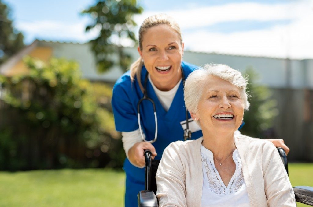 Elderly woman sitting on a wheelchair and being pushed by a nurse