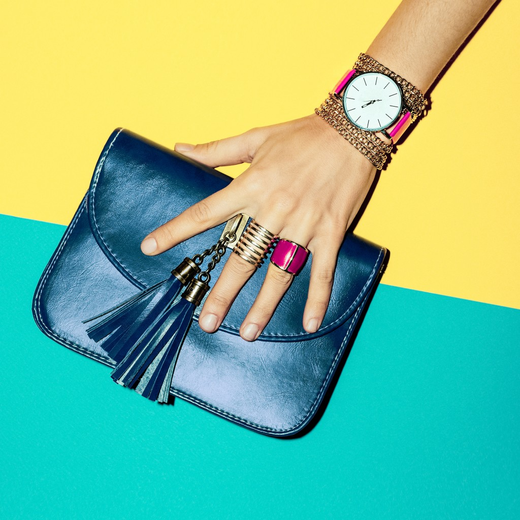 hand with bracelets, watch and rings holding a blue purse
