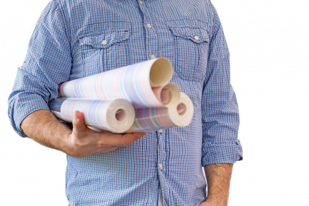 a man holding wallpaper