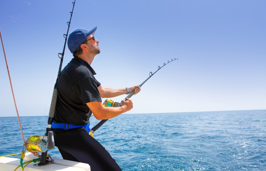 blue sea offshore fishing boat with fisherman holding rod in action
