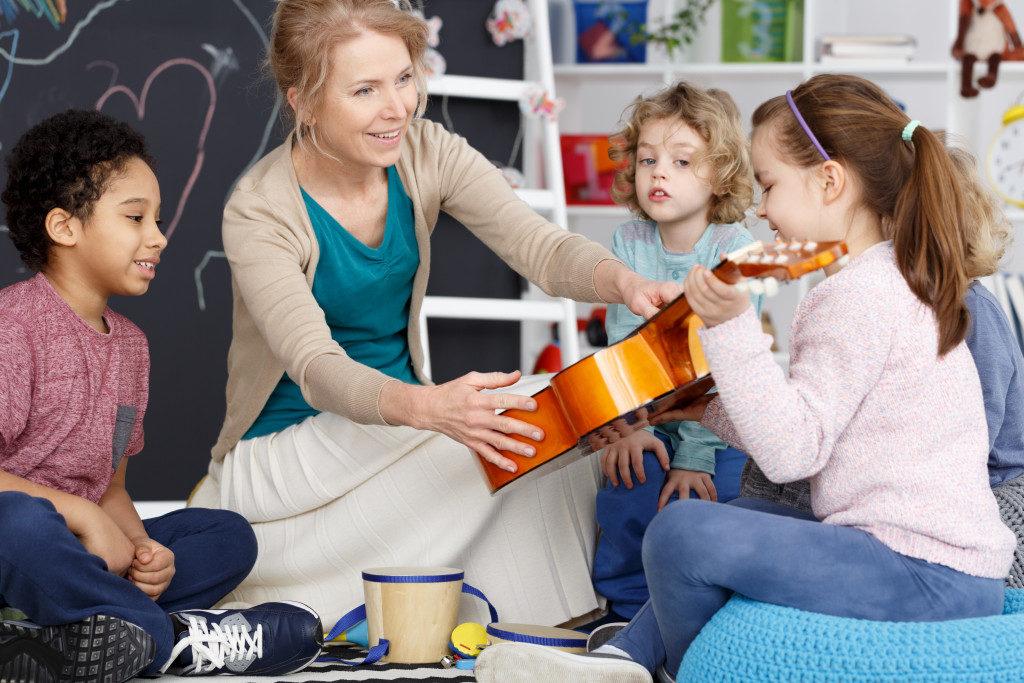 preschool students with their music teacher