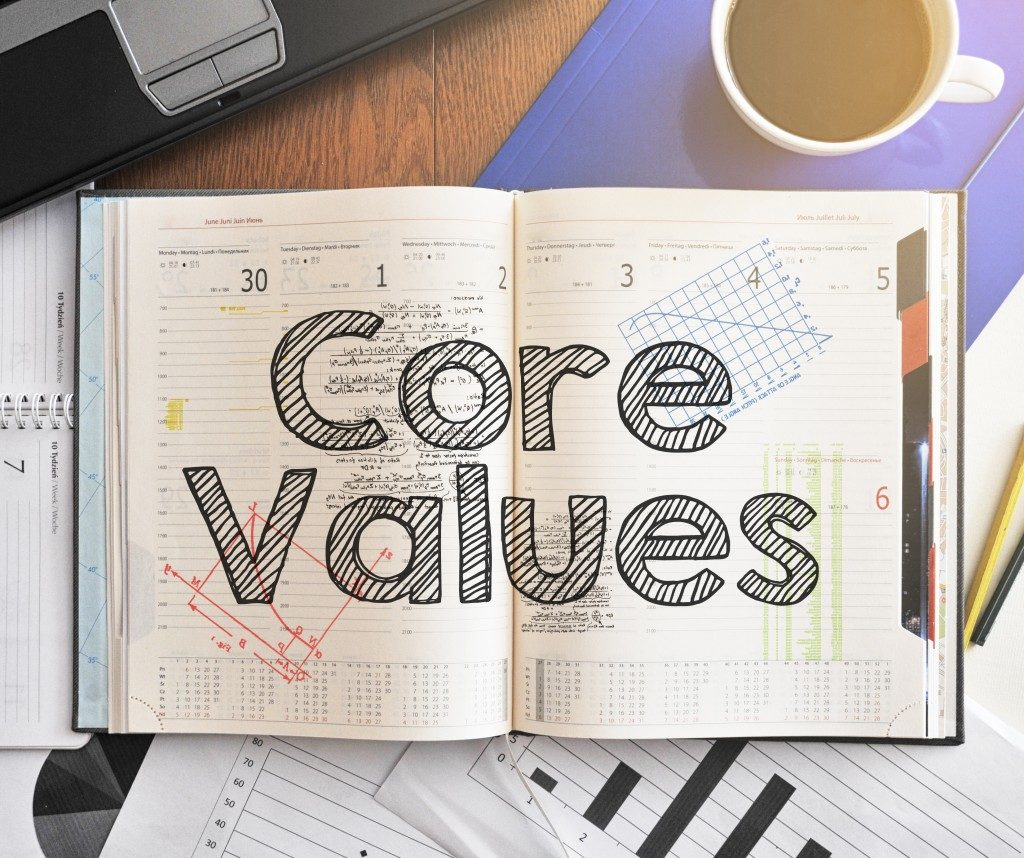 Notebook with text inside Core Values on table with coffee
