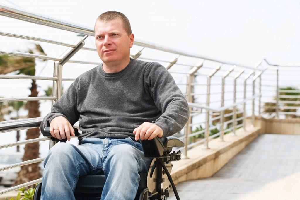 Man in wheelchair sits near the railing