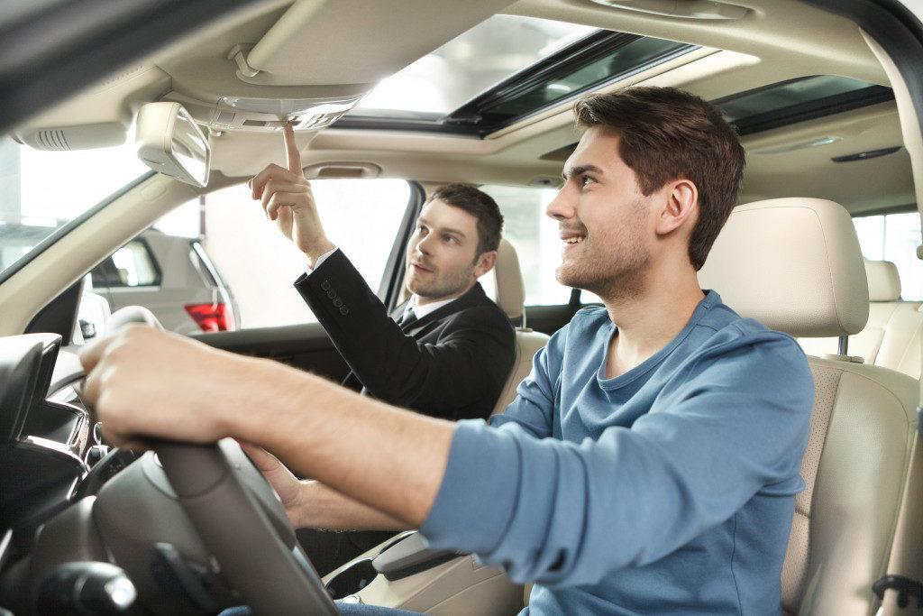 Car salesman explaining car to buyer