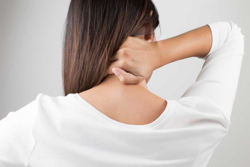 Young woman having pain in the back and neck