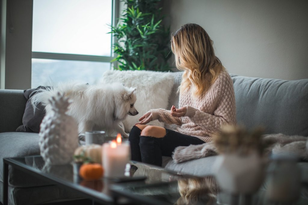 Woman with a dog on the sofa