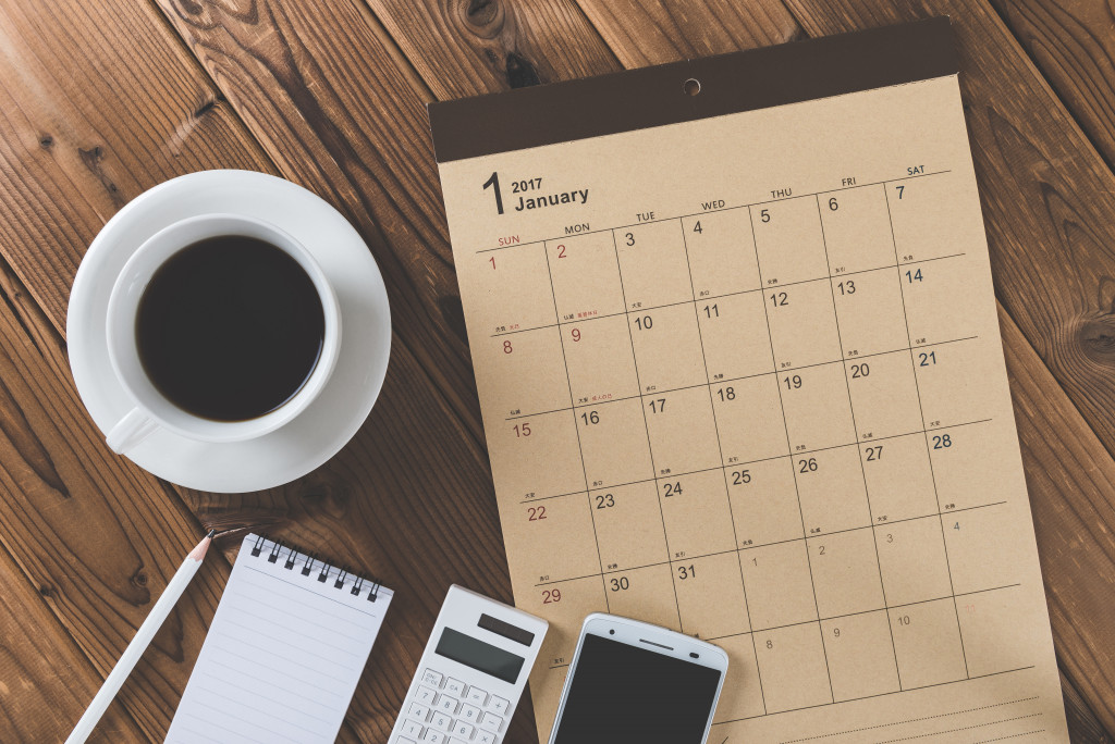 calendar, notepad, calculator, phone, and coffee cup on wooden background