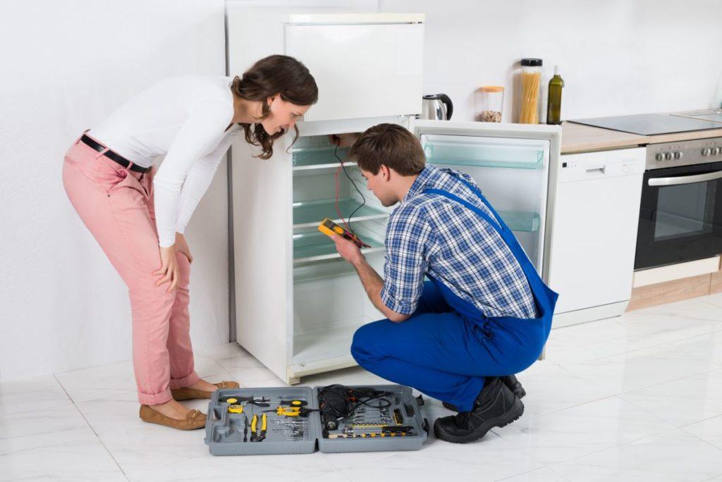 technician working on refrigerator