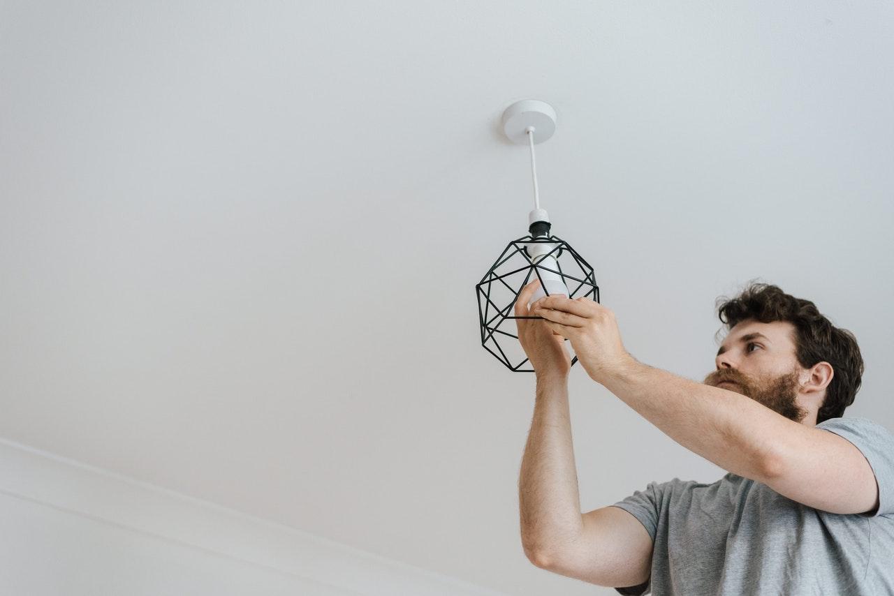 man replacing a light bulb