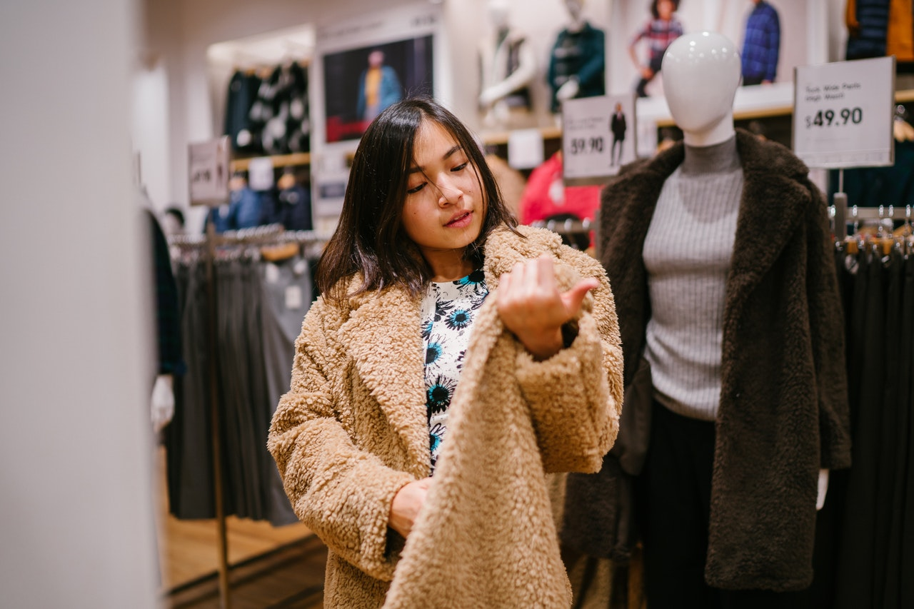 woman trying on a coat