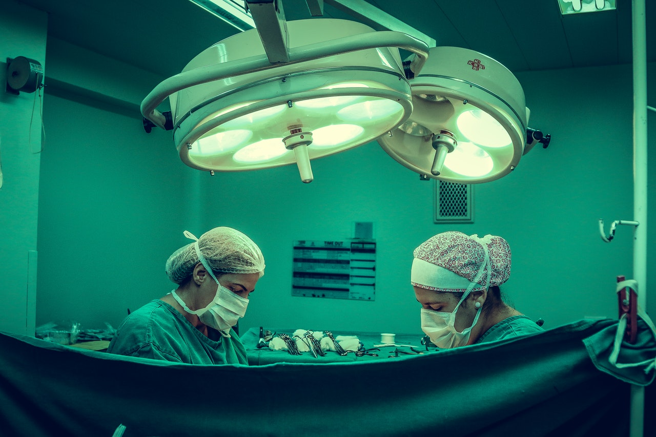 two surgeons operating on a patient