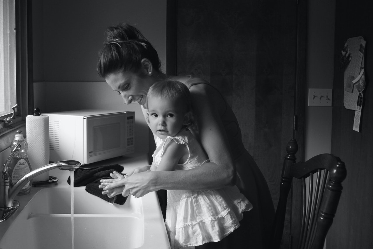 mother teaching toddler how to wash hands