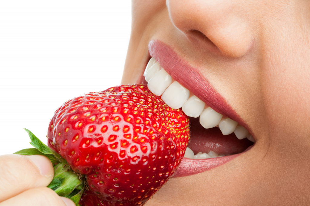 closeup biting strawberry